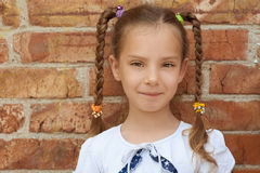 Beautiful little girl close-up. Portrait of smiling beautiful little girl close-up, against background of a brick wall Royalty Free Stock Photo