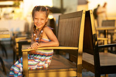 Beautiful little girl close-up. Portrait of smiling beautiful little girl close-up, sitting in chair Royalty Free Stock Image