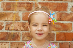Beautiful little girl close-up. Portrait of beautiful little girl close-up, against background of a brick wall Royalty Free Stock Photography