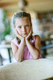 Beautiful little girl close-up. Portrait of beautiful little girl close-up, sitting on table Stock Images