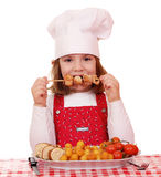 Little girl cook eat grilled chicken meat Stock Images