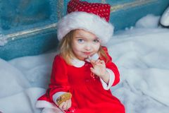 Cute little girl in Santa hat with cookies at home. Beautiful little girl with cookies for Santa Claus in festively decorated room Stock Photography