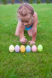 Beautiful little girl counts Easter eggs on green Royalty Free Stock Images