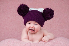 Beautiful little girl crying in the knitted cap on a pink background. Stock Image