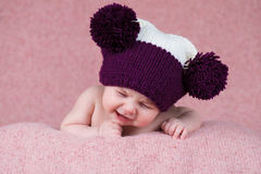 Beautiful little girl crying in the knitted cap on a pink background. Royalty Free Stock Images