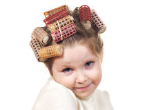 Beautiful little girl with curlers on her head. Stock Image