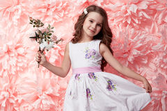 Beautiful little girl in cute dress with flower Stock Photo