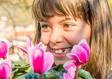Beautiful little girl with cyclamen flower Stock Photo
