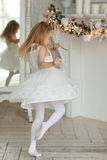 Beautiful little girl dancing and spinning, in the bright New Ye. Ar`s interior Royalty Free Stock Image