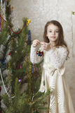 Beautiful girl decorates the Christmas tree. Stock Photo