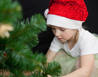 Beautiful little girl decorates the Christmas tree Royalty Free Stock Image