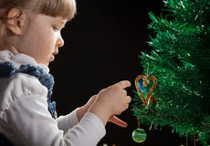 Beautiful little girl decorates the Christmas tree Stock Photography