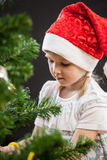 Beautiful little girl decorates the Christmas tree Royalty Free Stock Photos