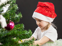 Beautiful little girl decorates the Christmas tree Royalty Free Stock Photo