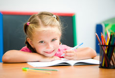 Beautiful little girl at the desk Royalty Free Stock Photos