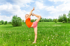 Beautiful little girl doing gymnastics on a grass Stock Photos
