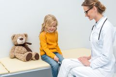 Beautiful little girl doing neurology examination for doctor with knee. Jerk hammer royalty free stock images