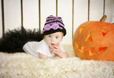 Beautiful little girl with Down syndrome sitting near a pumpkin on Halloween dressed as a skeleton Royalty Free Stock Image