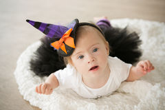Beautiful little girl with Down syndrome in a suit a little witch. Beautiful little girl with Down  syndrome in a suit a little witch Stock Photos