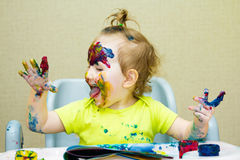 Beautiful little girl drawing in the album, Smeared face and hands paint, eyes. royalty free stock photography