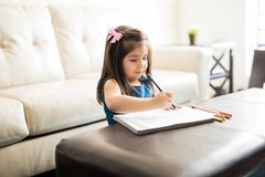 Beautiful little girl drawing and painting at home royalty free stock image