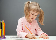 Beautiful little girl drawing with a red  pencil Stock Image