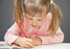 Beautiful little girl drawing with a red  pencil Royalty Free Stock Photos