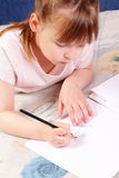 Beautiful little girl draws nice picture Stock Images