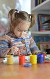 Beautiful little girl draws paint Stock Photos