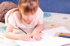 Beautiful little girl draws picture Stock Image
