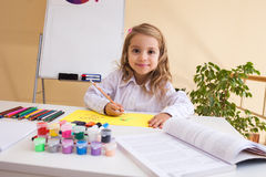 Beautiful little girl draws sitting at table Stock Photo