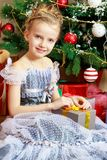 Little girl with a gift near the Christmas tree. Stock Photography