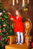Girl decorate a festive Christmas tree. Beautiful little girl in a dress, standing on an armchair and decorating a festive Christmas tree Royalty Free Stock Photography