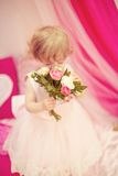 Beautiful little girl in dress. Beautiful little girl in white dress with toys Royalty Free Stock Photography