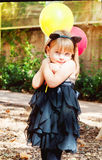 Beautiful little girl dressed as a cat with balloons in hands. Sweet smile, a tender look. Tricky glance Royalty Free Stock Images