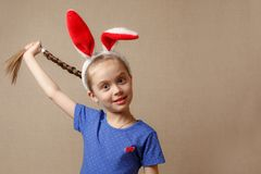 Beautiful little girl dressed in Easter bunny ears on a vintage background royalty free stock photo