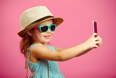 Beautiful little girl dressed in summer dress, wearing a straw hat and sunglasses, makes a selfie portrait on the phone stock images