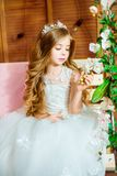 A beautiful little girl dressed in a summer white dress, with long curly hair Royalty Free Stock Image