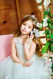 A beautiful little girl dressed in a summer white dress, with long curly hair Royalty Free Stock Images