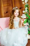 A beautiful little girl dressed in a summer white dress, with long curly hair Stock Photos