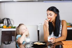 Beautiful little girl drinking milk and cookies Royalty Free Stock Photos