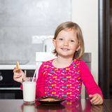 Beautiful little girl drinking milk with cookies. Stock Photography