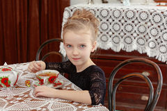 Beautiful little girl drinking tea at the table. Stock Images