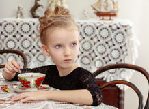 Beautiful little girl drinking tea at the table. Royalty Free Stock Image
