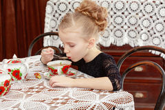 Beautiful little girl drinking tea at the table. Beautiful little girl drinking tea in the interior of the fifties of the last century. Retro style Royalty Free Stock Photos