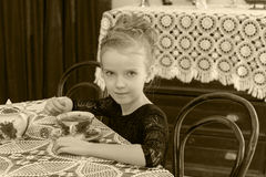 Beautiful little girl drinking tea at the table. Stock Photography