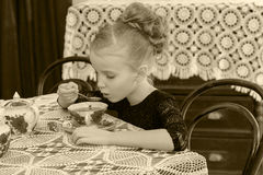 Beautiful little girl drinking tea at the table. Royalty Free Stock Photography