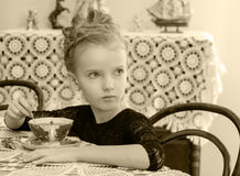Beautiful little girl drinking tea at the table. Stock Image