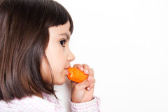 Beautiful little girl eating a carrot Royalty Free Stock Images