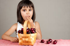 Beautiful little girl eating cherries. From a basket Royalty Free Stock Image